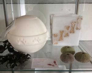 In het vierkante windlicht zijn hondenkluifjes verwerkt. De urn is gemaakt van zeezout.